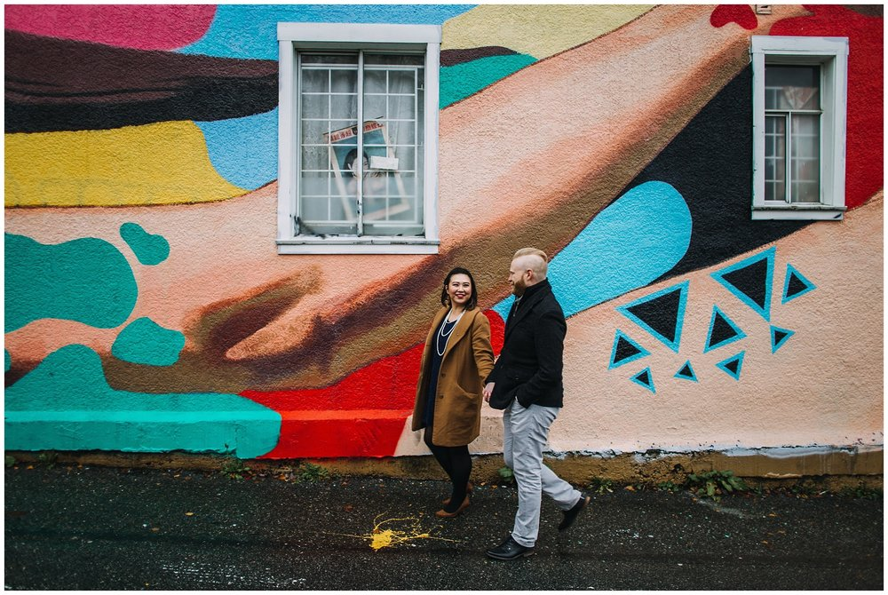 engaged couple walking in front of mural vancouver mural festival engagement photos