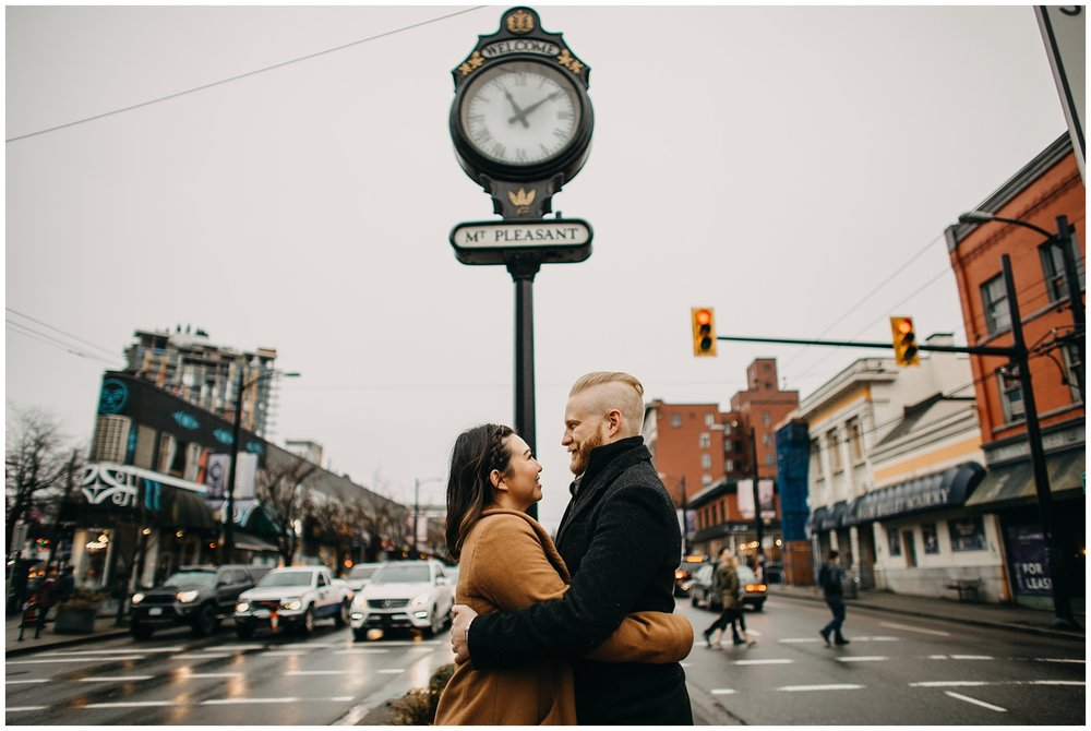 couple hugging in front of mount pleasant clock vancouver city engagement