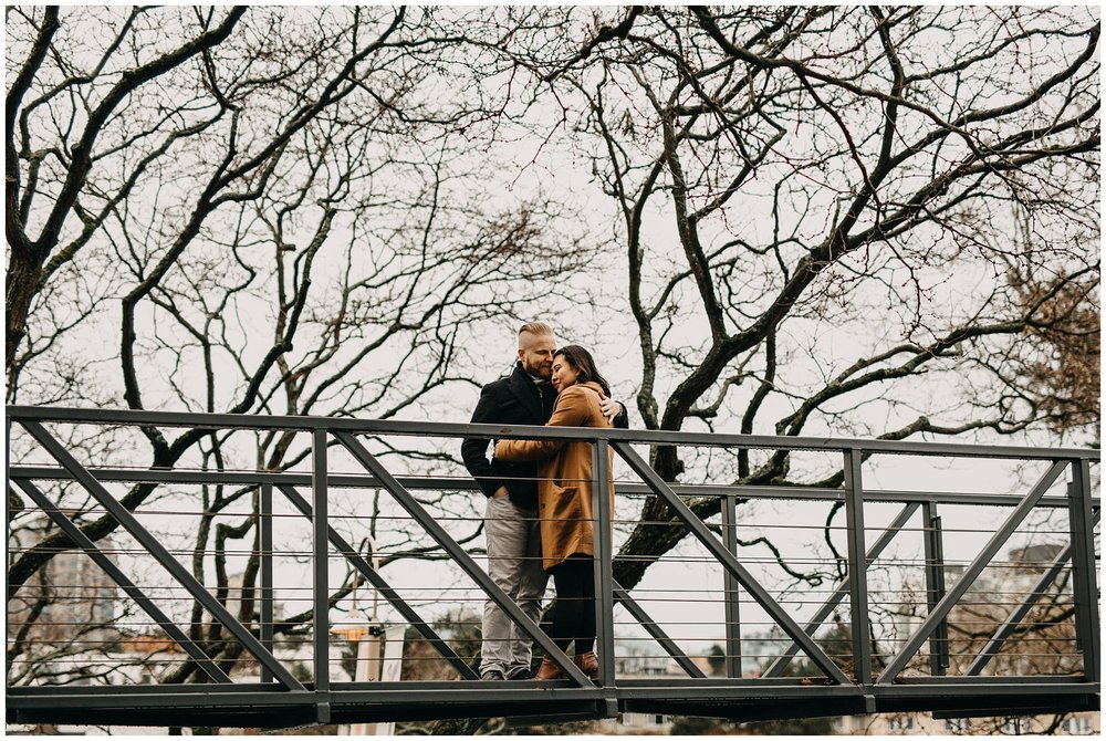 couple hug on bridge on granville island vancouver engagement