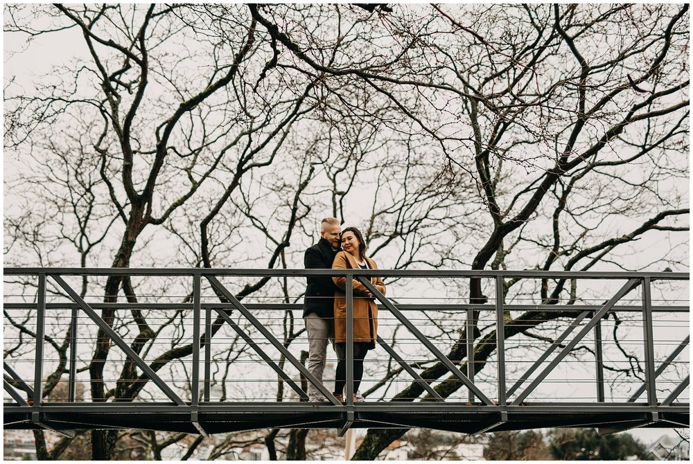 couple on bridge on granville island winter trees engagement