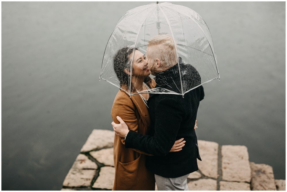 couple engagement rainy day granville island clear umbrella