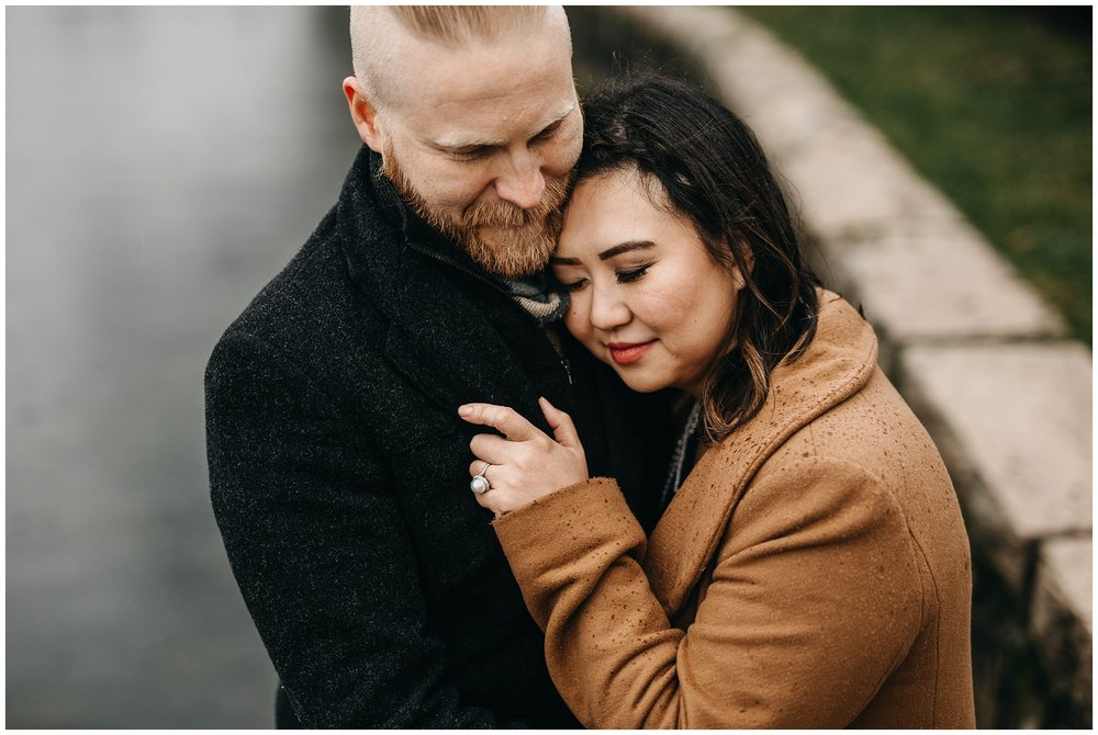 couple snuggle hug cold rain vancouver granville island engagement