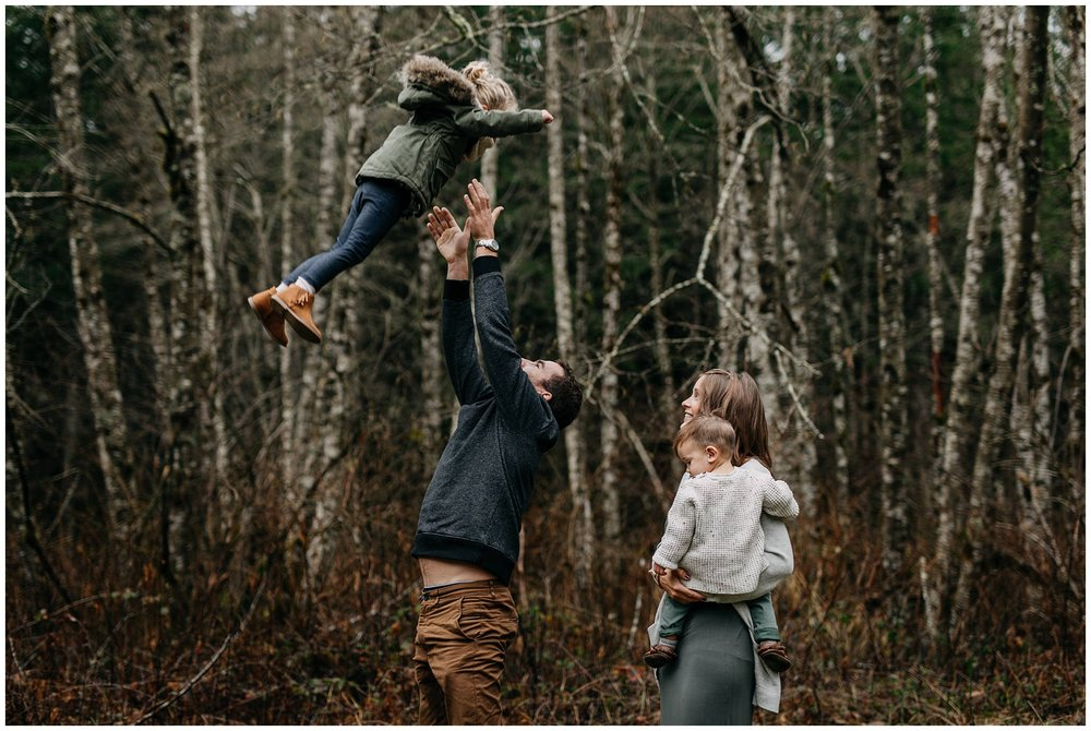 dad throwing daughter in air play fun family chilliwack forest trees