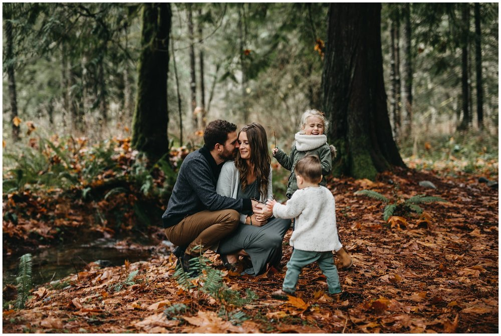 mom and dad snuggle kids playing around them chilliwack family photos