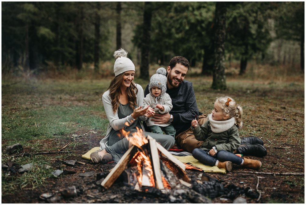 family sitting around campfire together on blanket chilliwack forest family photos