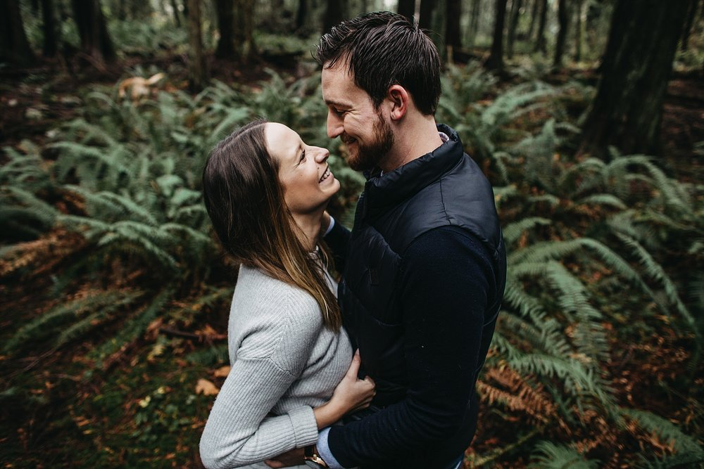 couple smile laugh engagement photos at pacific spirit park in forest
