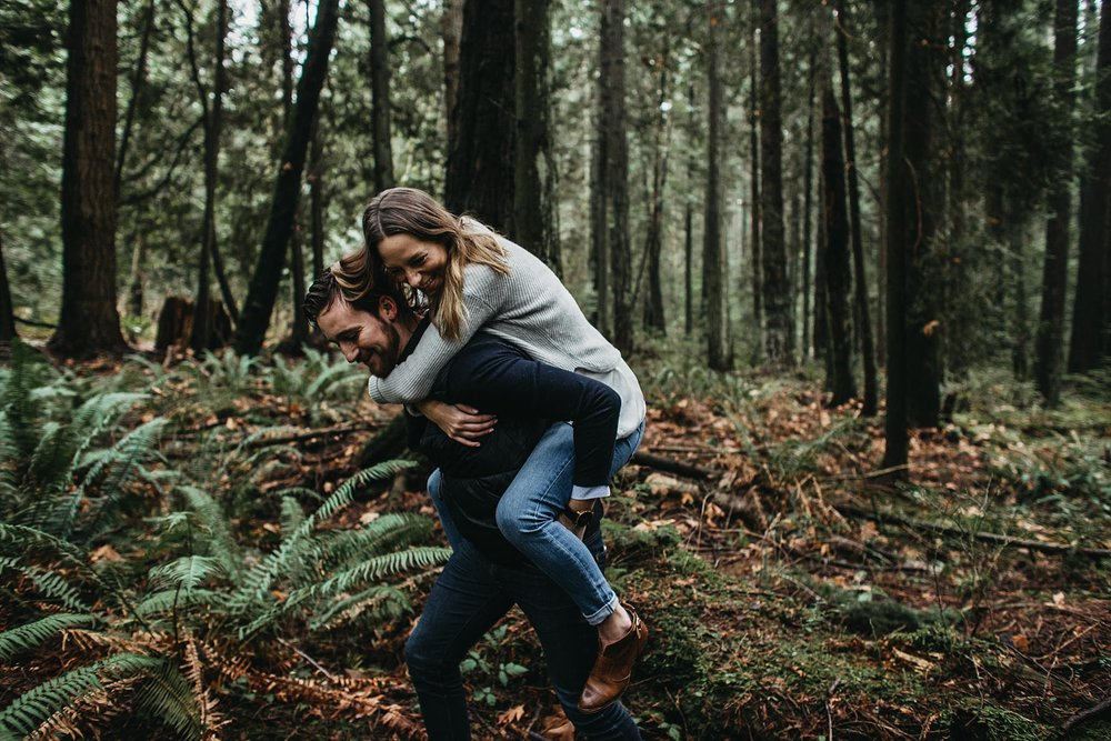 couple piggyback in forest of pacific spirit park