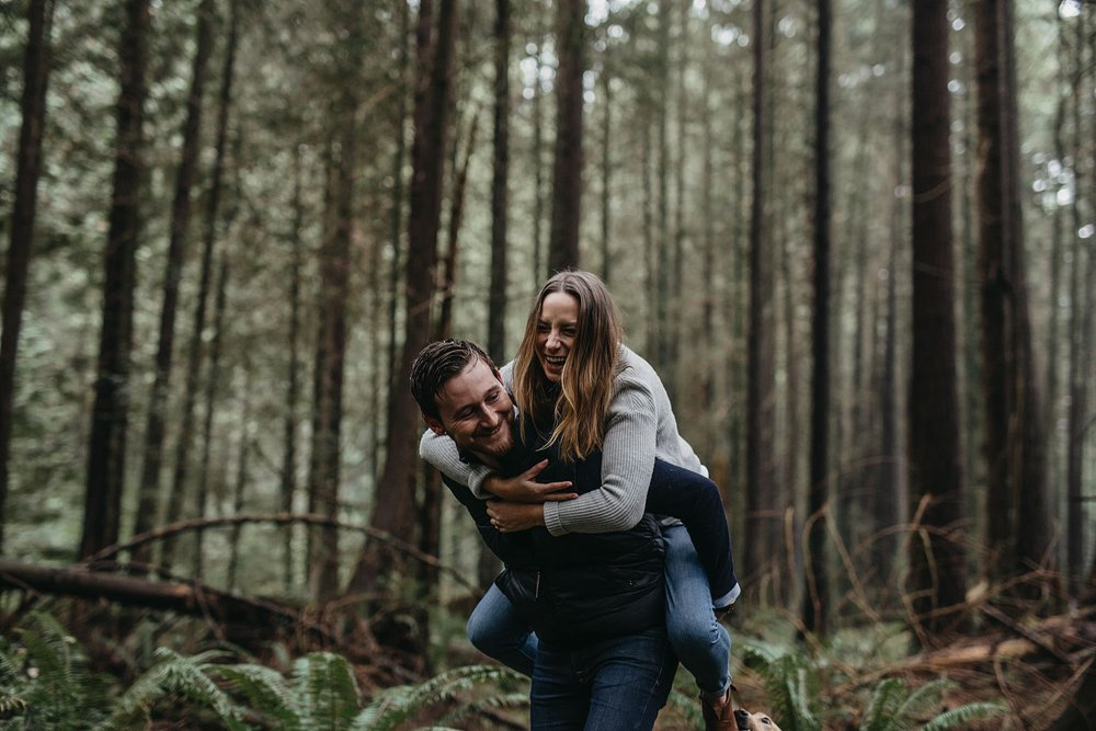 couple playful fun piggyback candid forest tall trees pacific spirit park