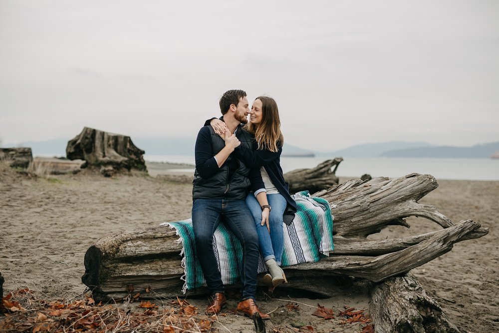 couple sitting on blanket on log spanish banks engagement