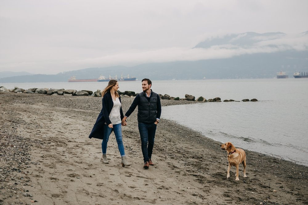 couple holding hands walking on beach with puppy spanish banks engagement