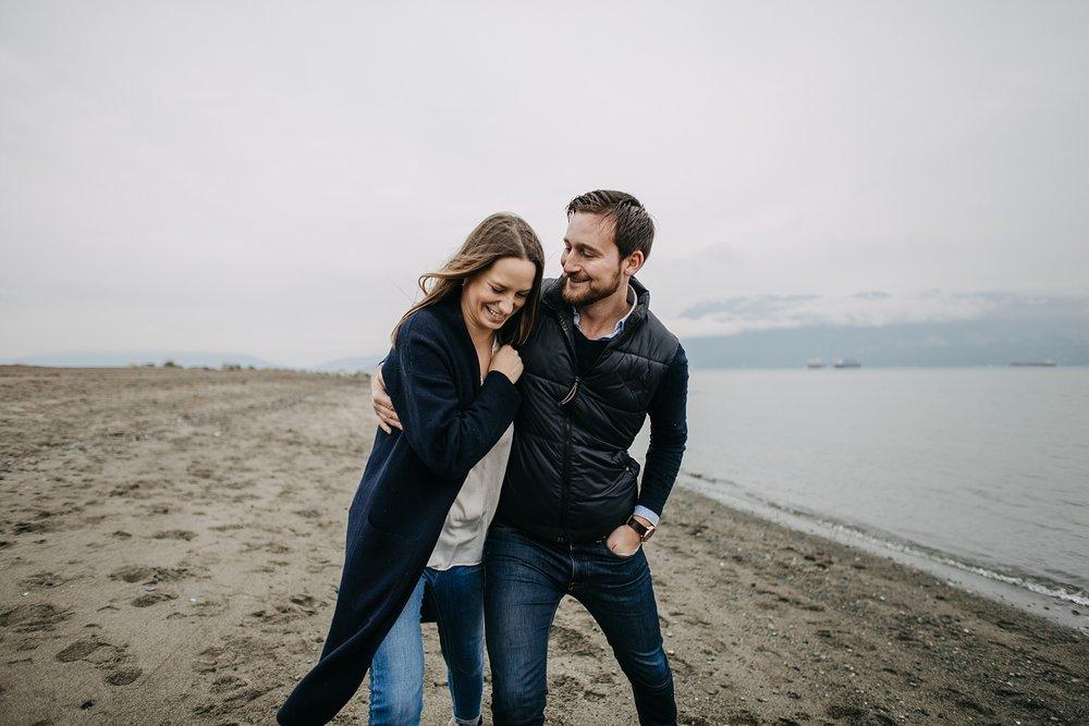guy making fiance laugh walking on beach spanish banks engagement