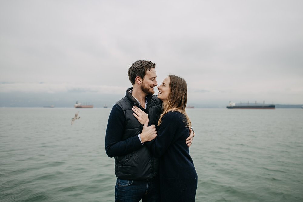 couple on dock by ocean pacific northwest spanish banks engagement