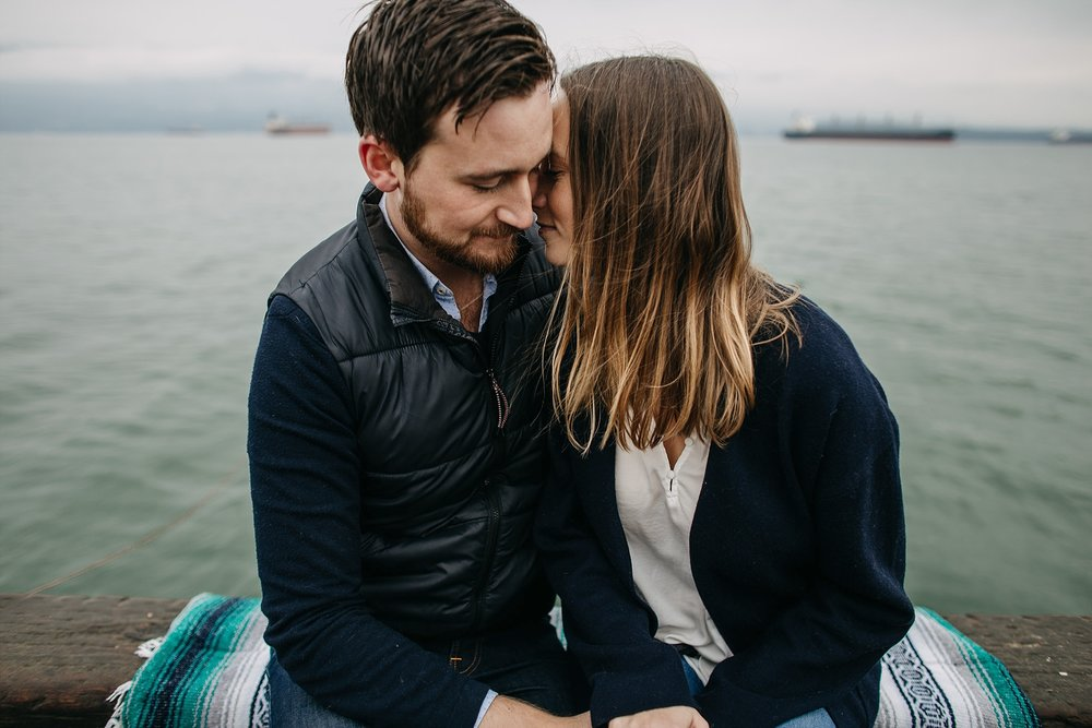 couple snuggling on dock by ocean spanish banks engagement