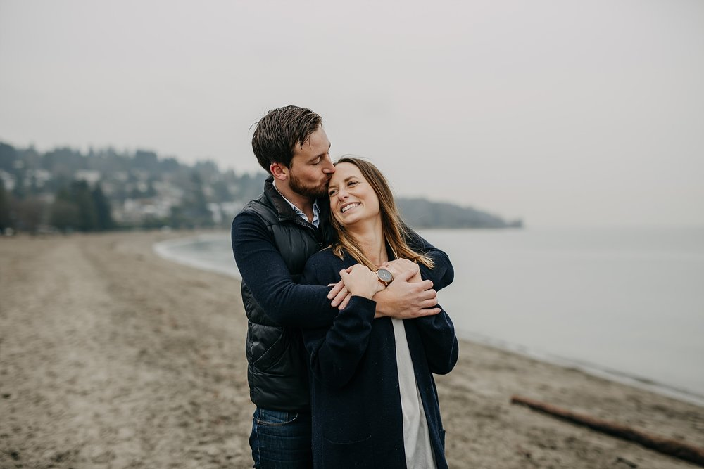 couple arms wrapped around kissing beach spanish banks engagement
