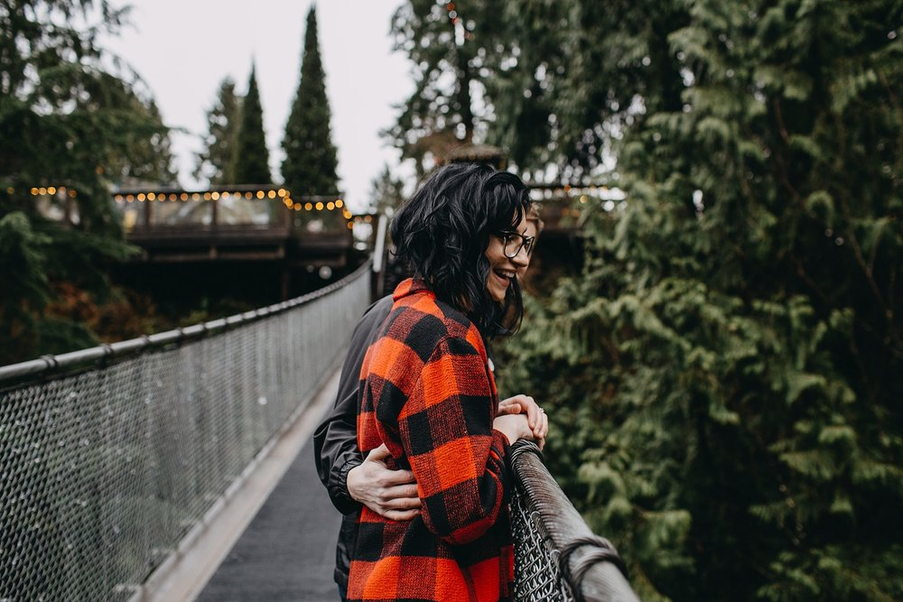 couple looking over capilano suspension bridge engagement