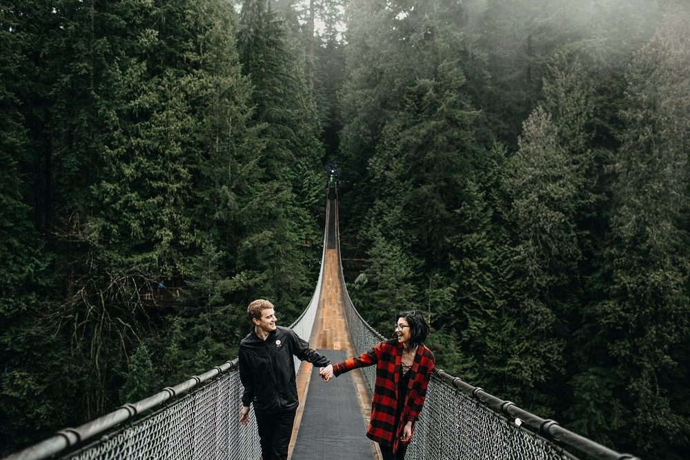 couple holding hands walking on capilano suspension bridge
