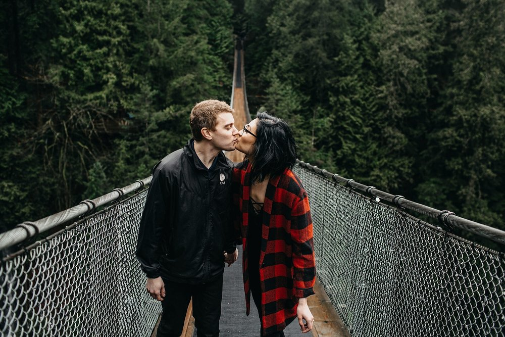 couple kissing on capilano suspension bridge engagement
