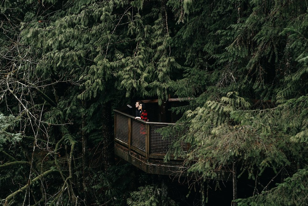 couple on lookout point trees forest capilano suspension bridge engagement