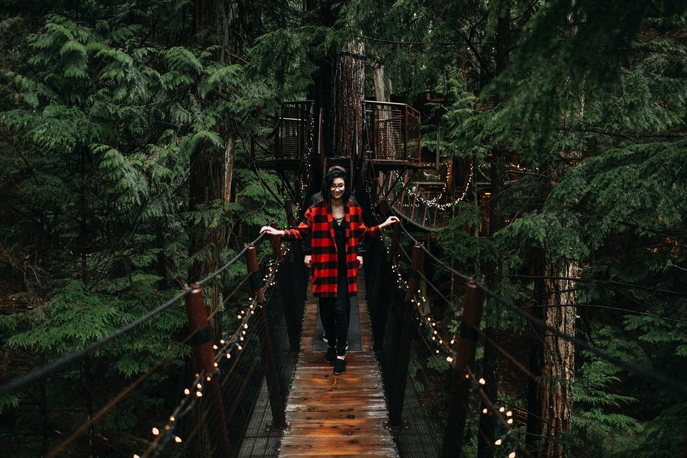 girl in red plaid walking on capilano suspension bridge