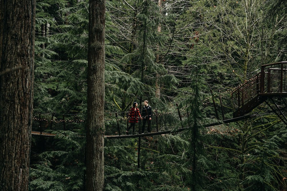 couple walking on tree top adventures engagement photos capilano suspension bridge