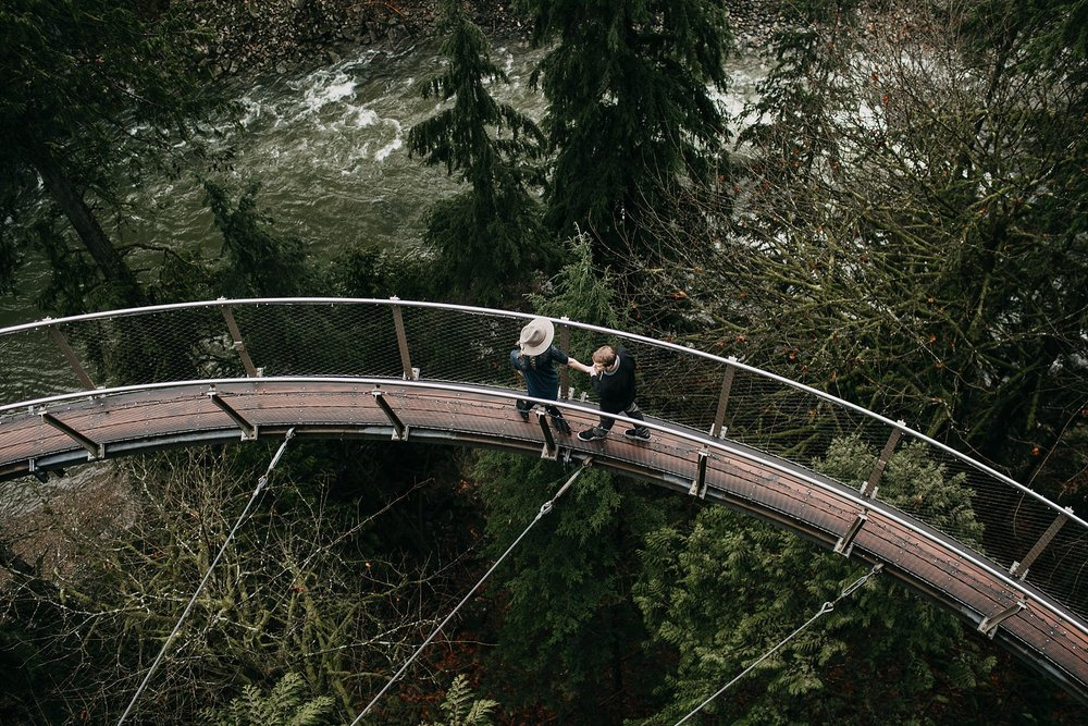 couple walking on cliff walk rainy day capilano suspension bridge green trees