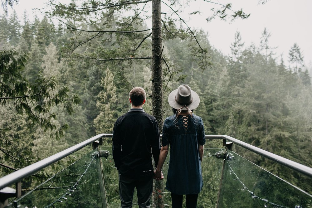 couple standing at lookout point capilano suspension bridge foggy rainy day