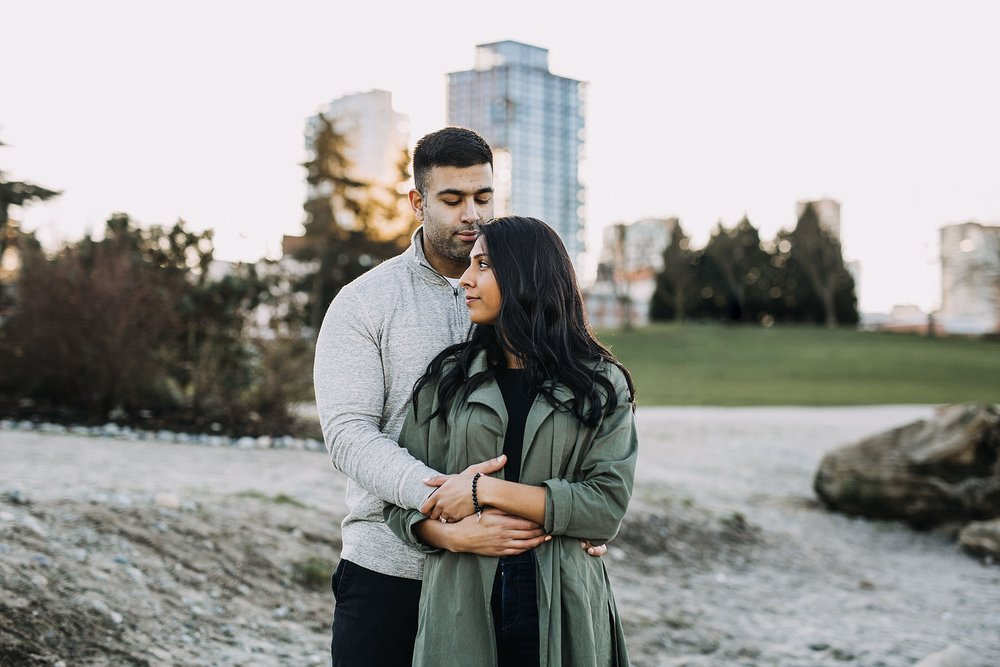 couple hug beach crab park city skyline vancouver engagement