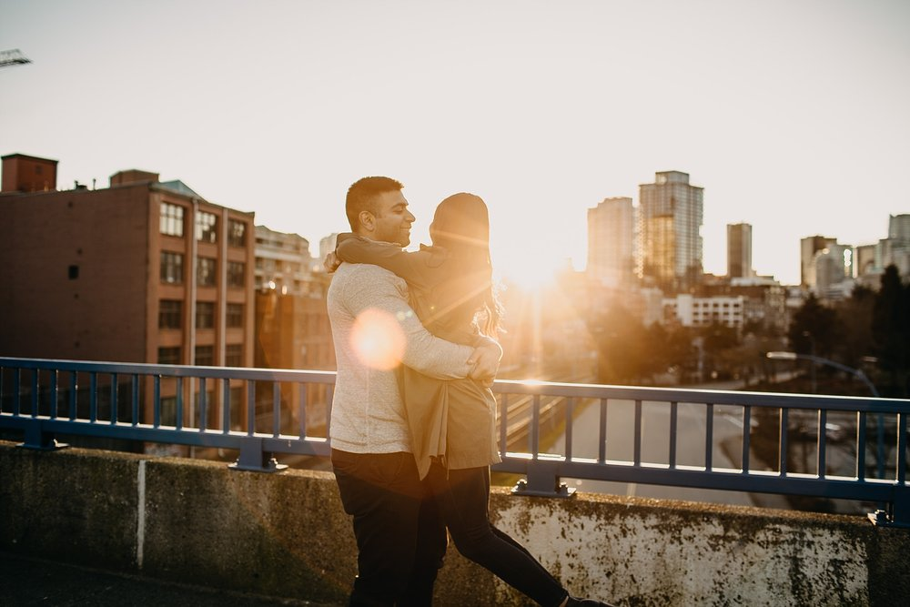 couple spinning in air sunset downtown vancouver engagement session