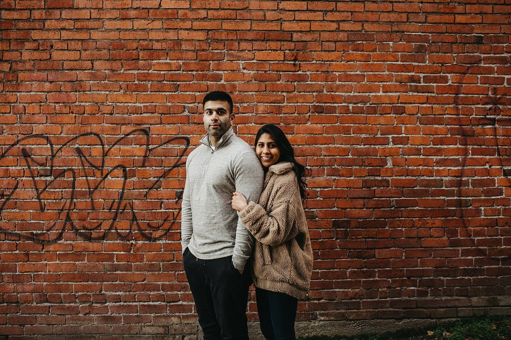 couple in front of brick wall downtown vancouver urban engagement