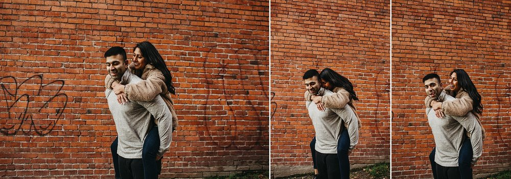 couple piggyback ride city brick wall downtown vancouver engagement