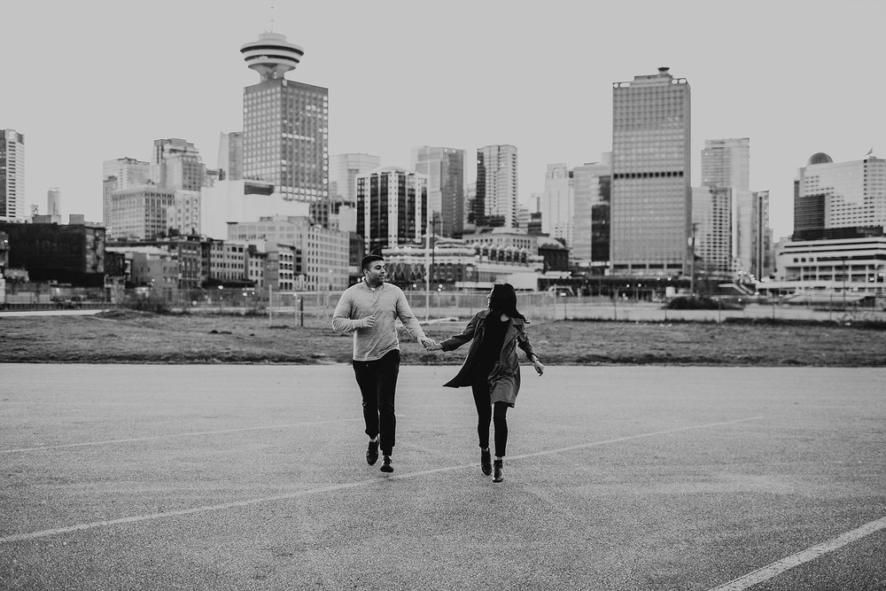 couple running city skyline behind downtown vancouver