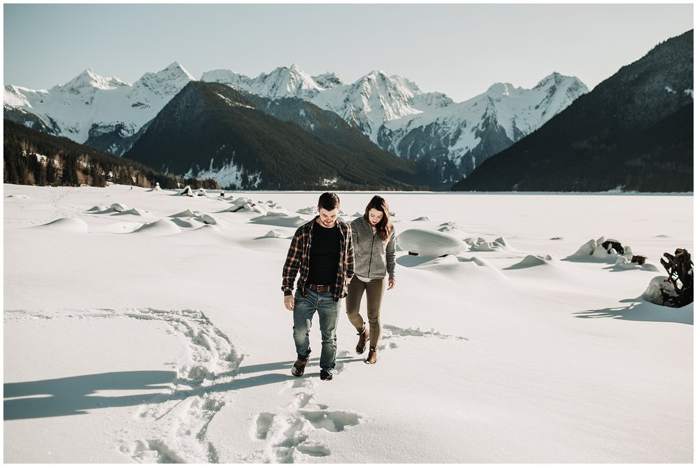 couple walking in snow at jones lake for engagement session