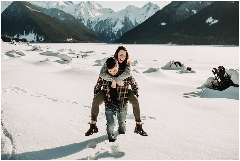 guy piggyback girl couple engagement session snowy jones lake