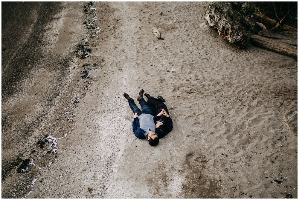 couple laying down on beach aerial shot engagement photos north vancouver