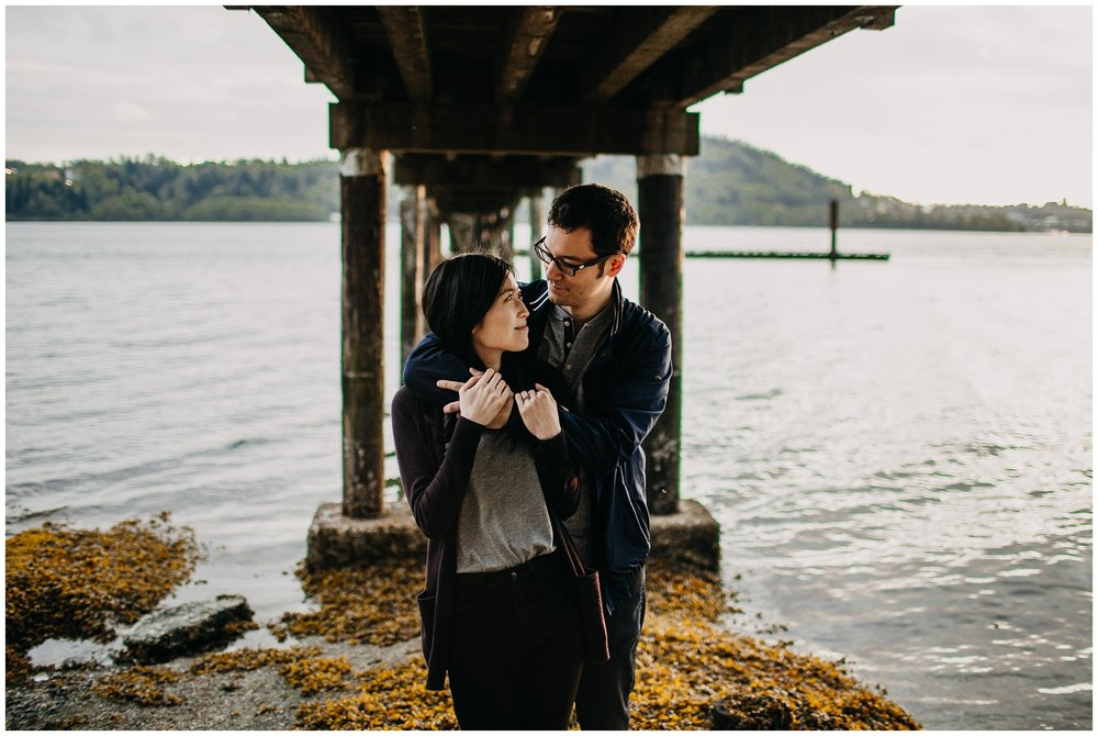 couple under dock beach sunset engagement north vancouver cates park