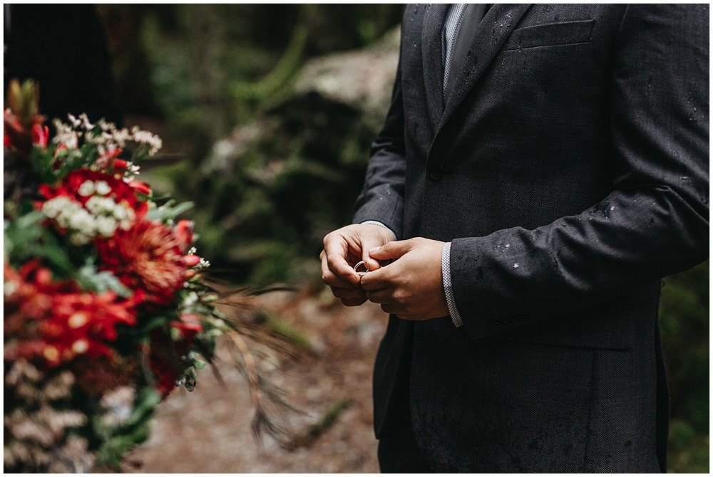 groom holding wedding band intimate forest ceremony golden ears wedding