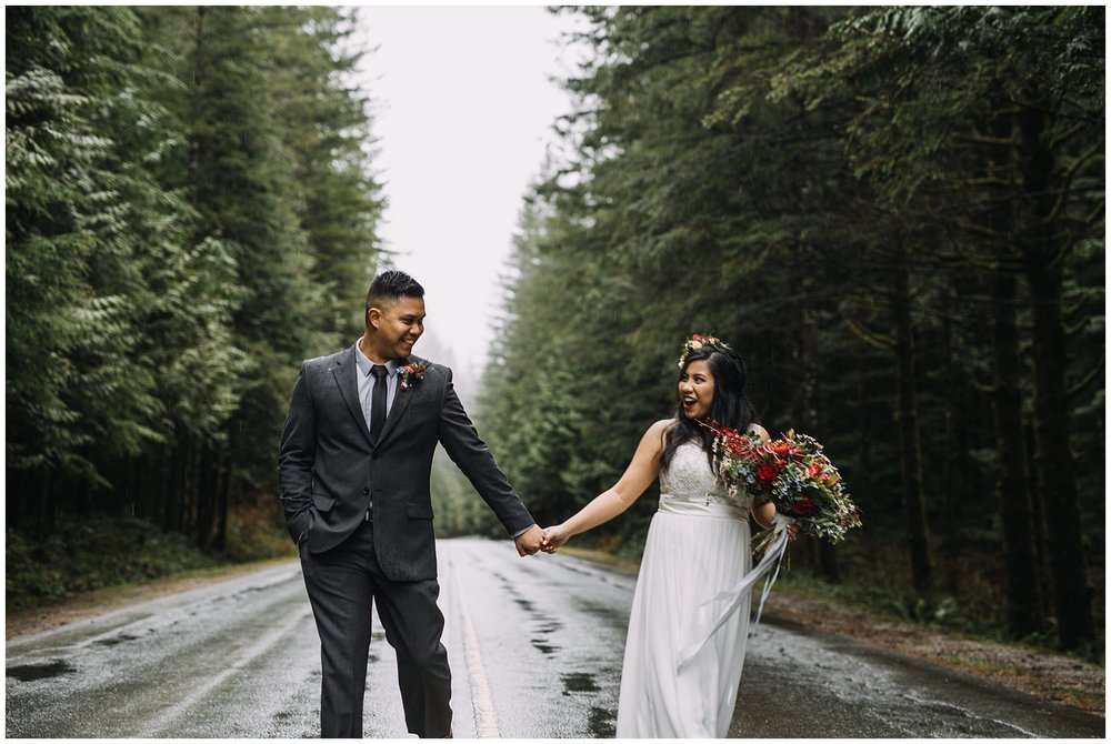 intimate golden ears wedding rainy day bride groom holding hands on road