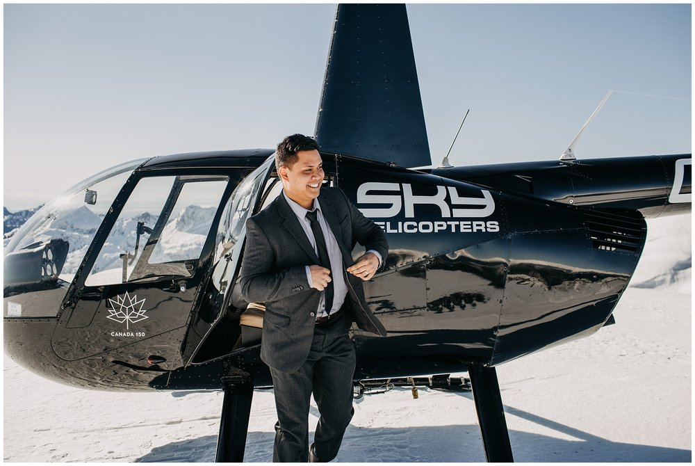 groom exiting sky helicopters snowy mountaintop wedding portraits