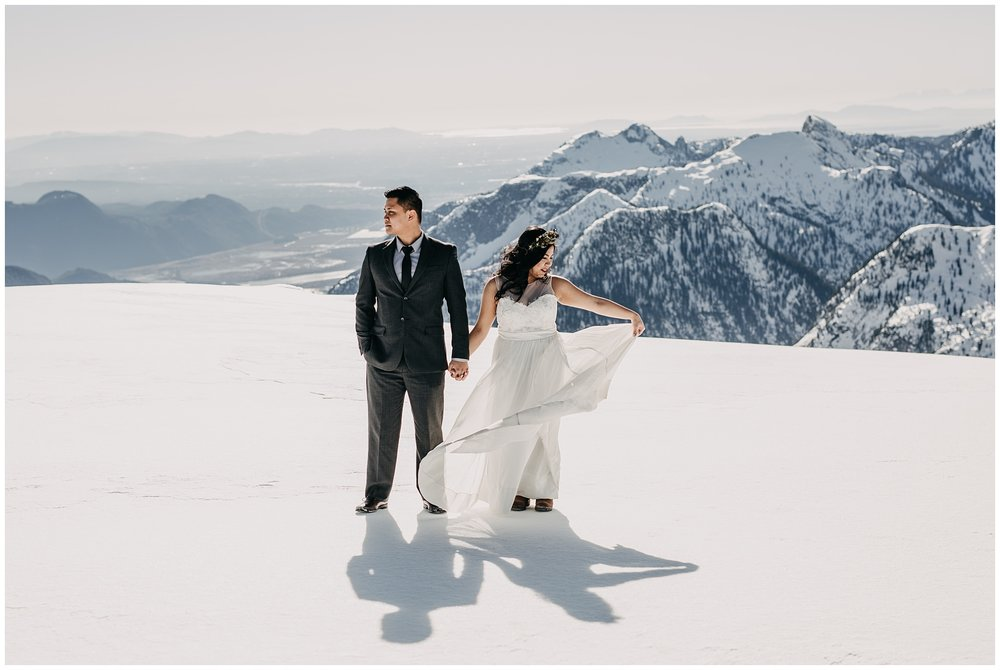 bride flowy wedding dress groom portraits mountaintop sky helicopters