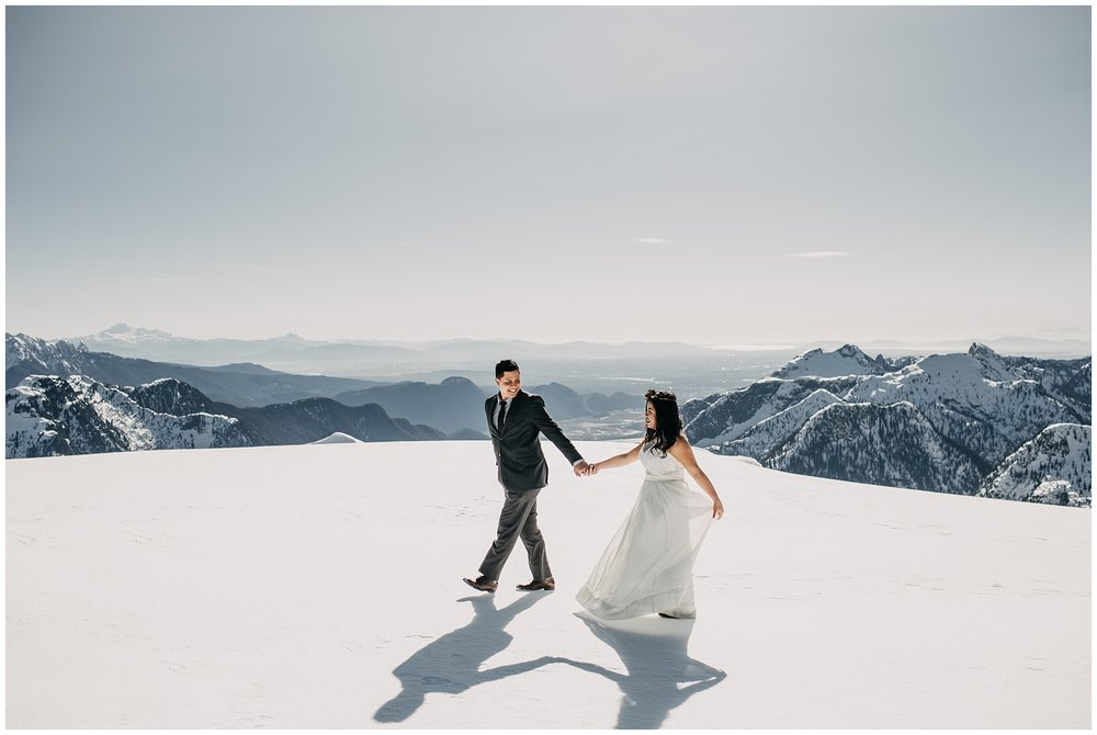 bride groom walking on snowy mountaintop sky helicopters wedding portraits