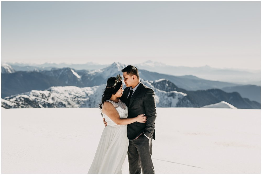 bride groom portrait on snowy mountaintop wedding day sky helicopters