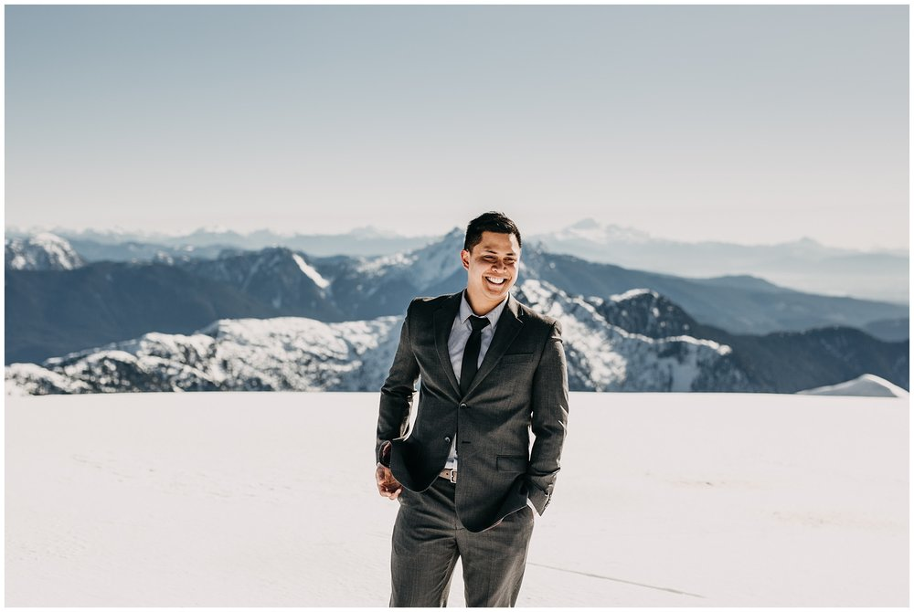 groom portrait suit mountaintop snow sun sky helicopters wedding