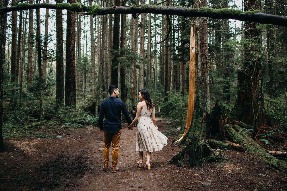 couple walking through forest pacific spirit park engagement session vancouver