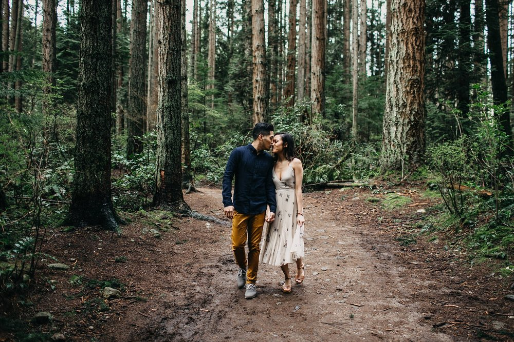 couple walking through forest kissing pacific spirit park engagement