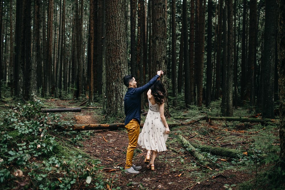 pacific spirit park engagement couple dancing in forest
