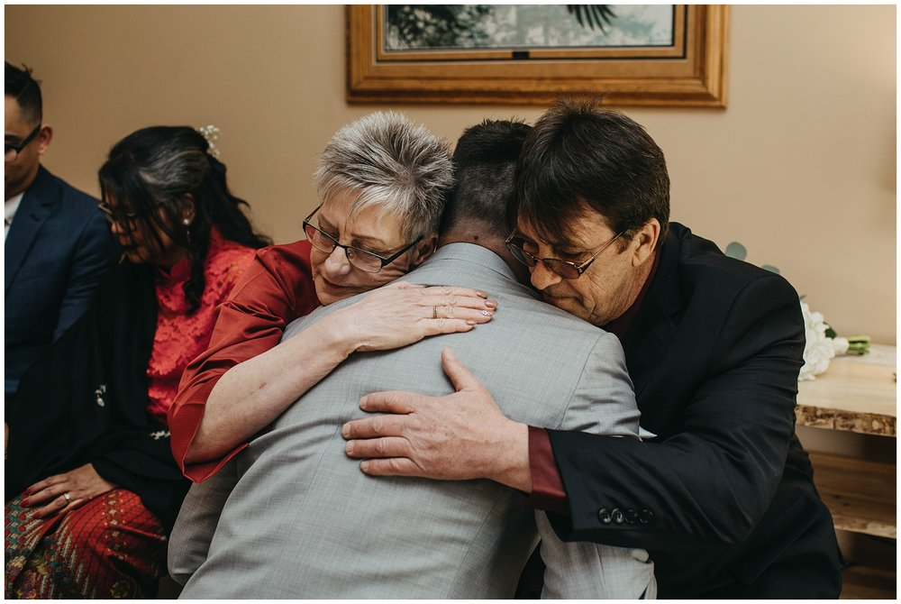 groom hugging parents emotional moment at fraser river lodge wedding