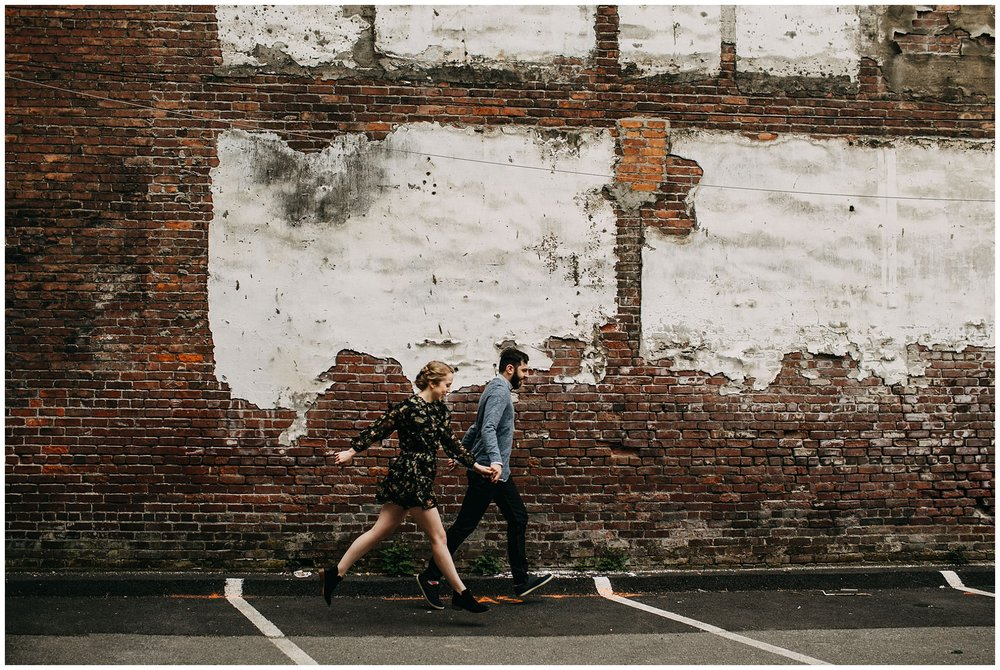 couple dancing in front of brick wall at downtown new west engagement session