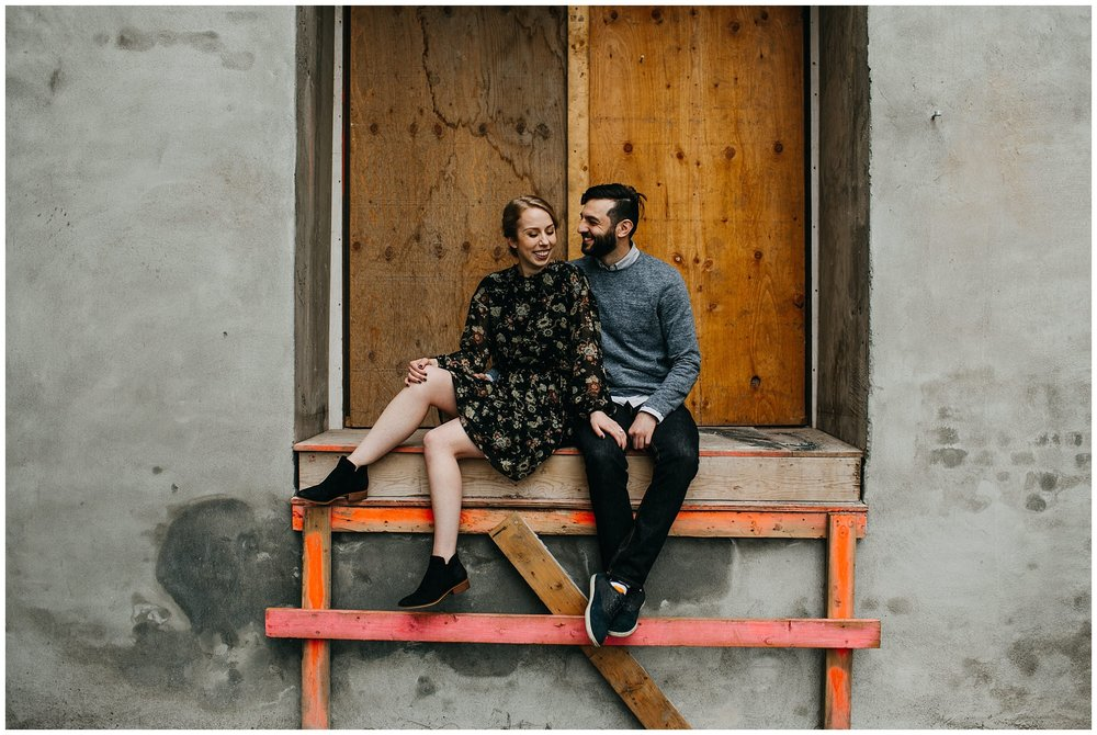 couple sitting in urban setting at downtown new west engagement session