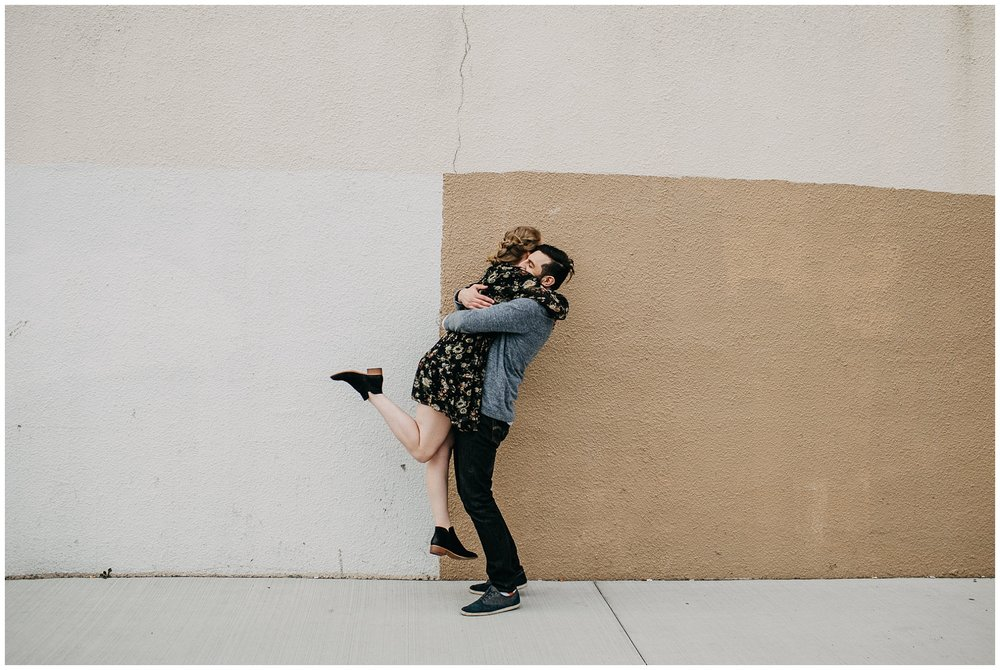 couple hugging in urban setting at downtown new west engagement session