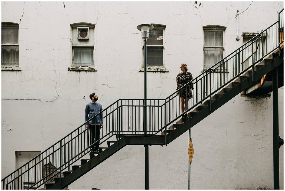 couple standing on stairs at downtown new west engagement session